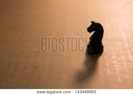 Silhouette single chess knight on cardboard .