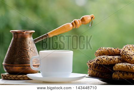 Copper Cezve coffee mug and delicious cookies on the table green background