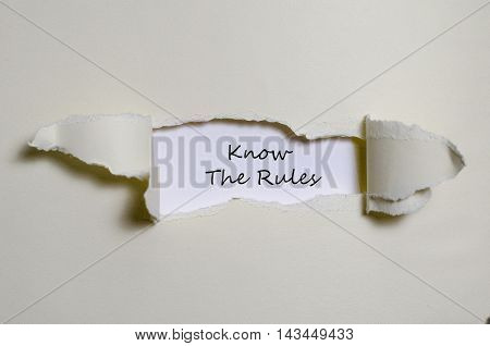 The words know the rules appearing behind torn paper