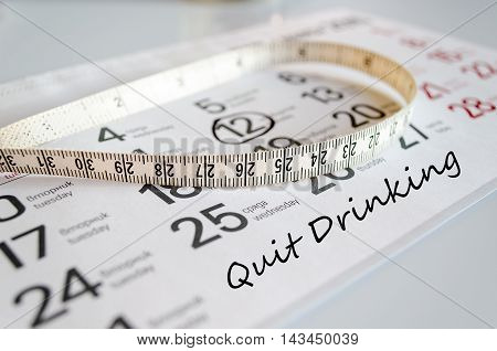 Quit drinking text concept over tape measure and calendar background