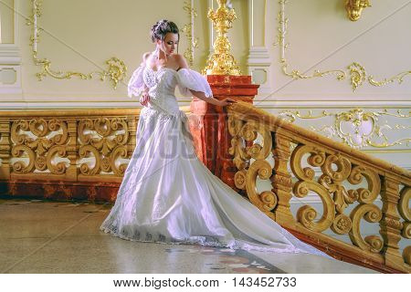 a charming young lady in a luxurious white dress is going upstairs in the unique theatre