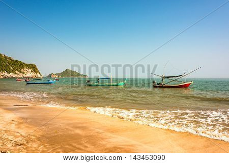 Tropical beach with sand shore and clear turquoise blue water and clear sky with colourfully decorated traditional Thai boats on shoal. Kui Buri Leam Sala Thailand