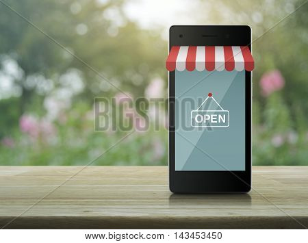 Modern smart mobile phone with on line shopping store graphic and open sign on wooden table over blur pink flower and tree