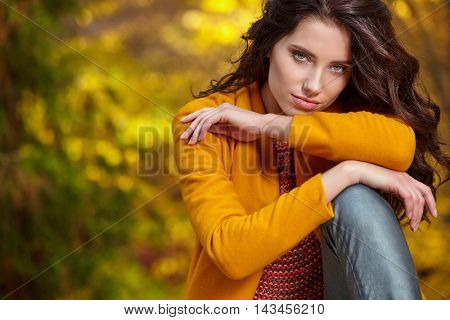 Beautiful young woman in autumn styling on the background of autumn park