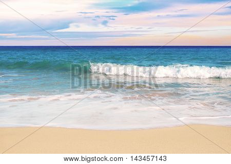 Tropical beach in the evening, sunset scene with colorful sky and waved rolling on the beach.
