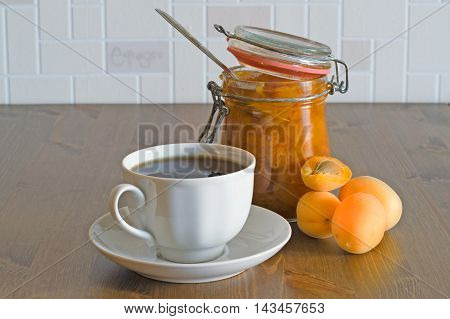 Homemade organic apricot jam with spoon in opened in glass jar with apricots and tea on wooden table