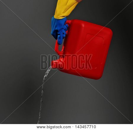 Hand holding jerrycan on dark grey background