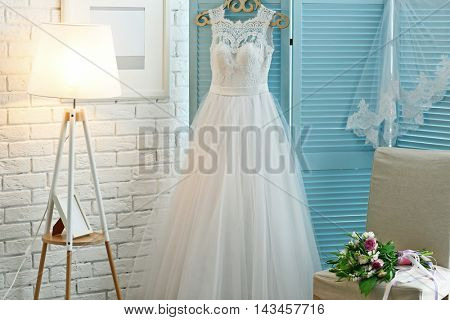 Beautiful wedding dress on hanger in room