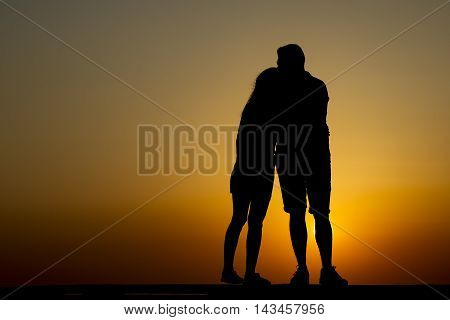 Young couple at sunset holding hands and happy,