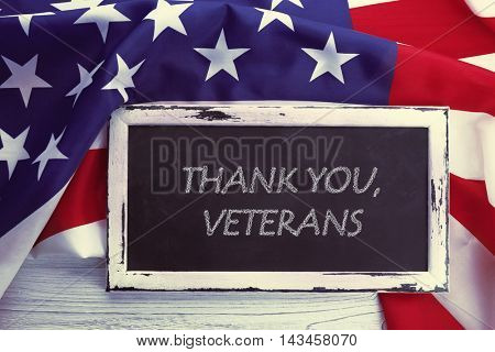 Blackboard with text THANK YOU, VETERANS on USA national flag