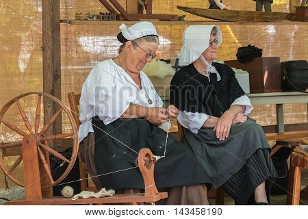 Woman Using An Antique Spinning Machine To The Wire