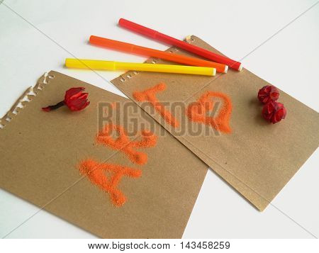 Copyspace blank sheets of craft paper covered with multiple colorful felt pen marke, dried flowers and orange sand