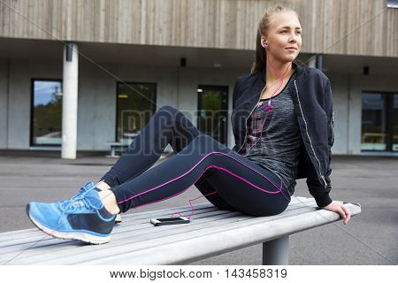 Beautiful woman sits on a bench in the city wearing a jacket and sportswear. Listens to music and using smart phone.