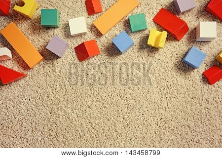 Colorful wooden building blocks for children on carpet, top view