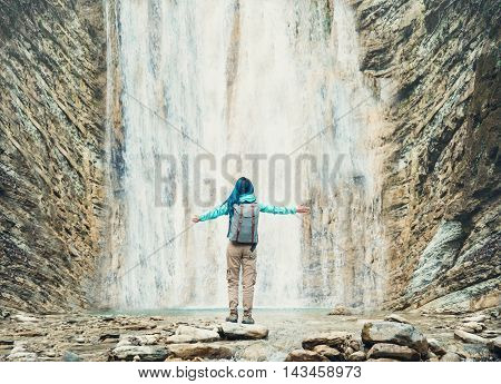 Happy explorer young woman with backpack standing with raised arms in front of beautiful waterfall