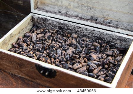 Beans in a wooden box. Many Legumes beans lentils. Texture of the raw beans moon striped colors. Storage of loose grains in a natural box.
