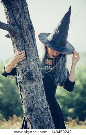 Beautiful young woman in costume of witch standing near the tree outdoor. Theme of Halloween and magic