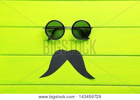 Black Sunglasses And Mustache On A Green Wooden Table