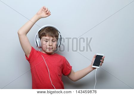 Portrait Of Young Boy With Headphones And Smartphone On Grey Background