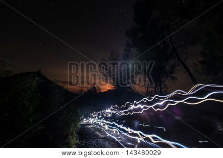 Long exposure, lights line of tourist traveler hiking up to the top of Kawah Ijen mountain at night with stars