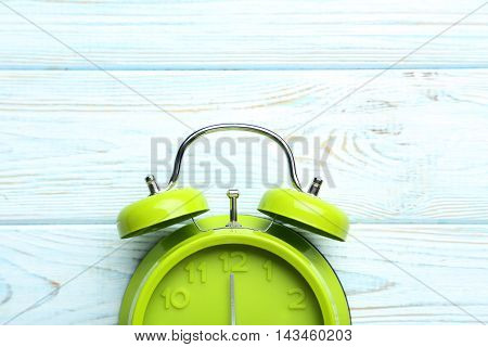 Green Alarm Clock On A Blue Wooden Table