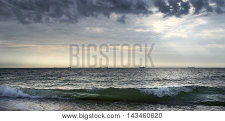 Sunrise Seascape with ships on the horizon and cloudy sky