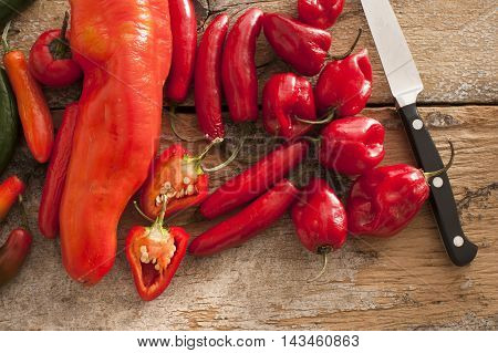 Small assortment of round and thin red hot peppers besides a stainless steel knife on a rustic table