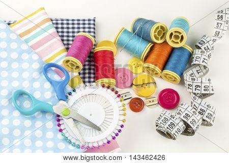 Sewing items in basket: threads, pins, meter and scissors on white