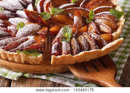 Sliced Plum Tart Close-up On The Table. Horizontal