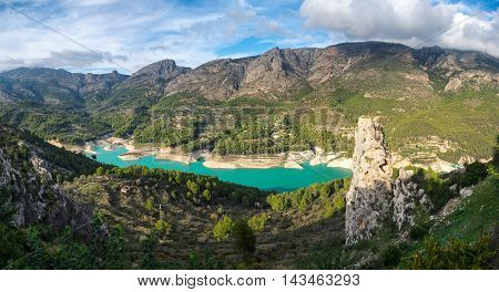 Panorama of Guadalest - a small village. Heavy clouds lie at the mountains and blue lake.