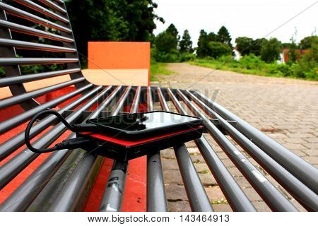 A black smartphone and a red powerbank on a bench in a park