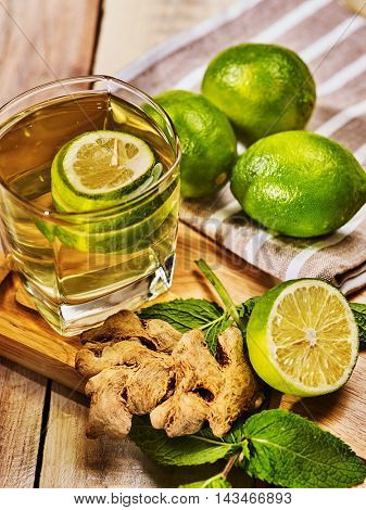 Healthy detox drink with ginger . On wooden boards glass with green tea and mint. Mint ginger drink number two hundred eighty two with half lime and napkin. Country top view. Light boards background.