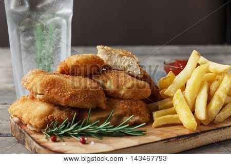 chicken nuggets french fries on the board with red sauce