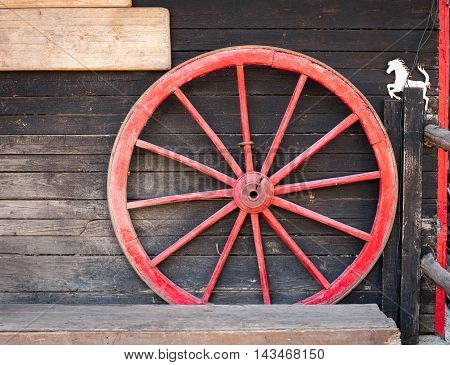 Big red cart wheel on wooden wall with little white horse symbol country style