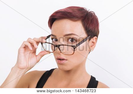 Surprised young lady with short hair dyed red and in glasses and black tank top. Concept of mild astonishment. White background.