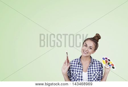Girl with palette and paintbrush standing against light green background. Concept of creation. Mock up