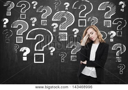 Stressed woman standing near chalkboard with many question marks on it. Concept of too many questions. FAQ.