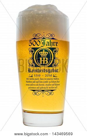 Munich Germany - June 11 2016: Glass of cold Bavarian beer with frothy foam head backlit isolated on white with text 500 years of Reinheitsgebot - German Beer Purity Law