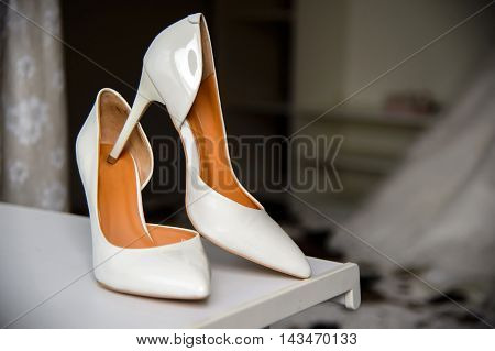White lacquer wedding shoes bride. Women's elegant shoes. Dressing the bride and wedding accessories.