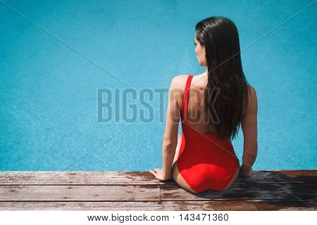 woman in red swimsuit sitting near the pool summer tan