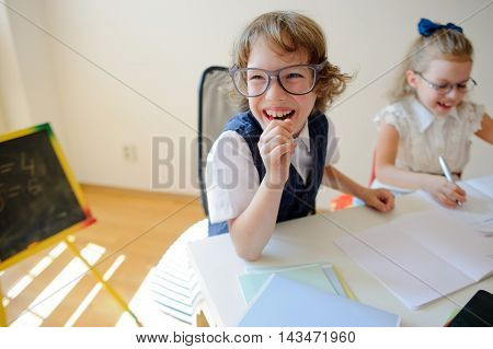 Ridiculous little students bespectacled boy and girl share the same desk. They are pupils of an elementary school. They laugh. On the desk in children are school supplies and textbooks. Back to school