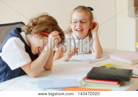 Cheerful small students share the same desk. They are pupils of an elementary school. Boy and girl laugh. On a school desk children have school accessories and textbooks. Back to school.