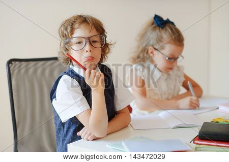 Funny little pupils sit at one desk. They are pupils of an elementary school. Boy fools around girlie writes something with a serious look. On a school desk children have school accessories and textbooks.