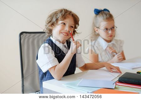 Funny little pupils sit at one desk. They are pupils of an elementary school. Boy fools around at girl a serious look. On a school desk children have school accessories and textbooks. Back to school.