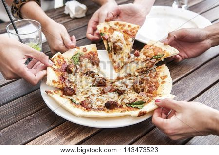 People taking slices of pizza and sharing drinks.