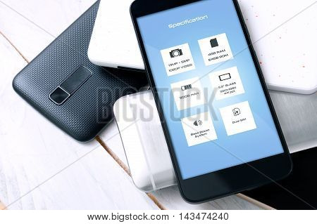 Smartphone with specification on screen laying on another unknown smartphones. Concept of making a decision which smartphone to choose