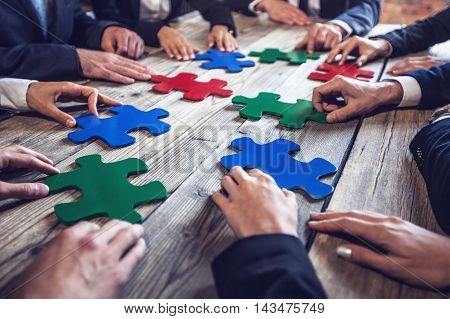 Business people and puzzle on wooden table teamwork concept