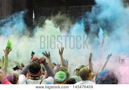 STOCKHOLM SWEDEN - MAY 22 2016: Happy audience with arms in the air and blue color powder in the air in the Color Run Event in Sweden May 22 2016
