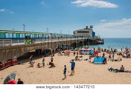 BOURNEMOUTH, UK - 09 AUGUST 2016: Pier Amusements and beach in a summer sunny day.