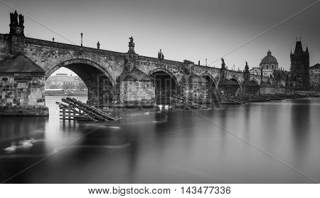 Black and white view on the Charles Bridge with statues and tower in the mist. Magical picture of the medieval gothic bridge and baroque statues in the historical center of Old Town Prague Europe